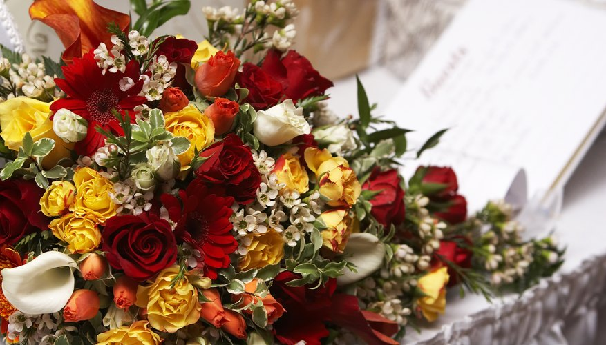 A guestbook on a table next to a large bouquet of flowers.