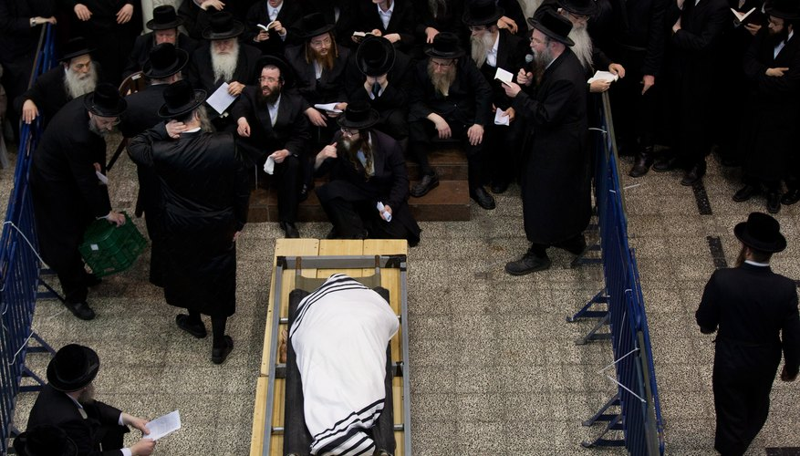 An Orthodox Jew is wrapped in a white linen shroud and tallit.