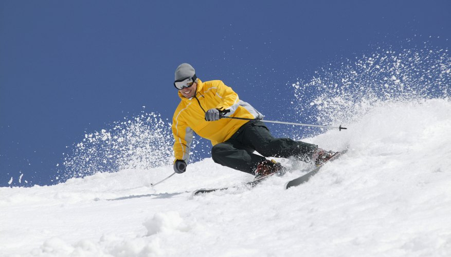 Man downhill skiing in snow.