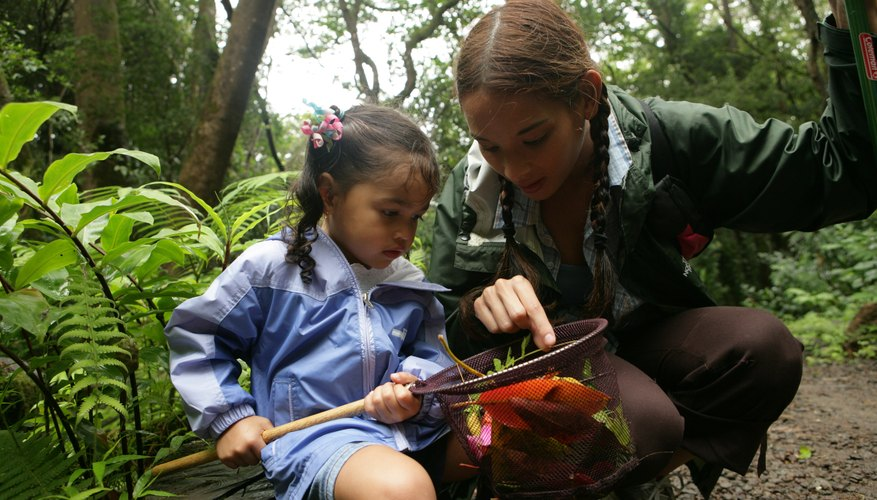 Two young girls inspect an insect while on a field trip at a sanctuary.