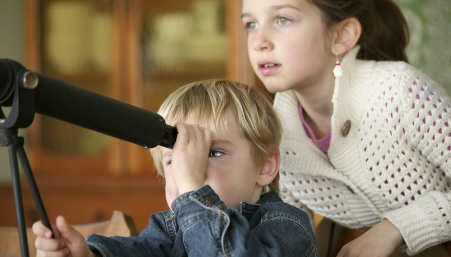 Young children looking through telescope