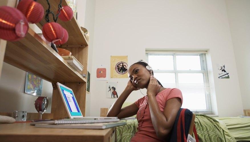 Girl with laptop in dorm room.