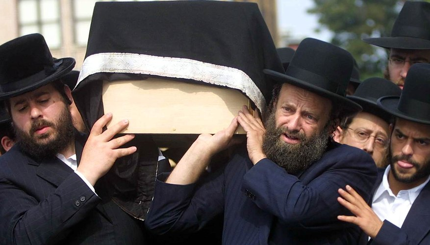 Orthodox Jews carry a traditional, unadorned pine casket.