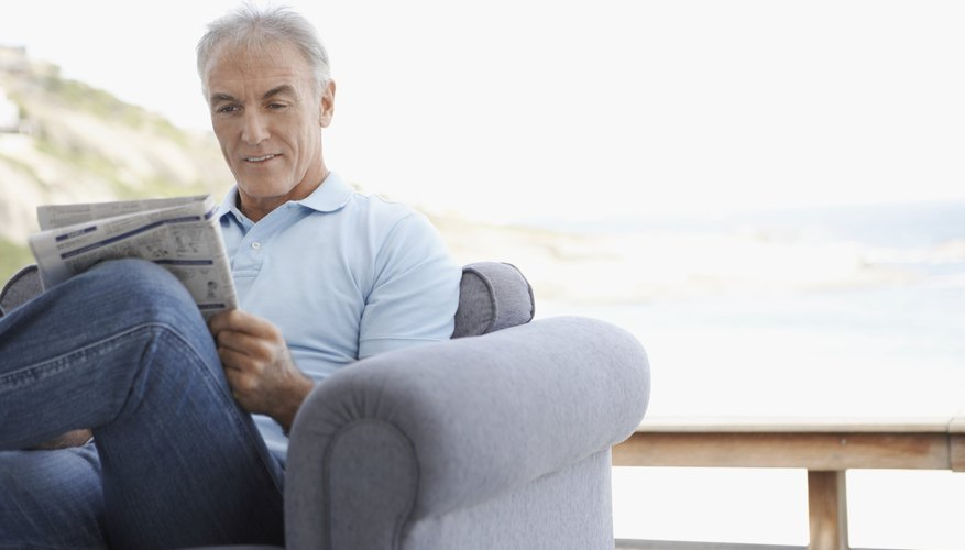 Man reading newspaper in chair.