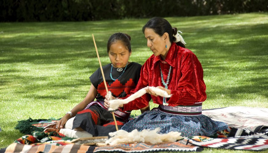 A Navajo woman teaches a young girl how to use a drop spindle to spin yarn.