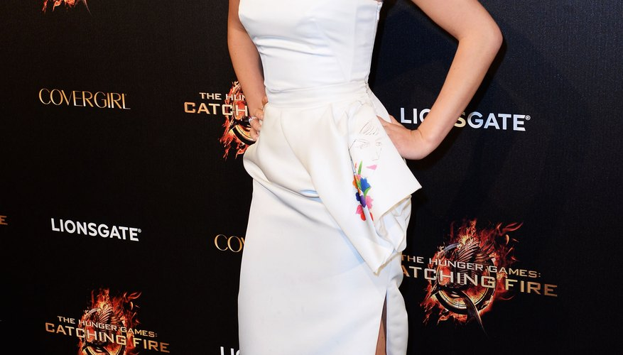 Jennifer Lawrence sports a pair of hot pink heels with a sleek and structured white dress.