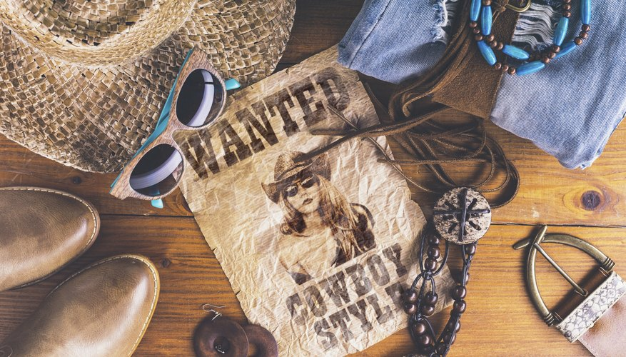 Cowboy accessories surrounding a wanted poster.