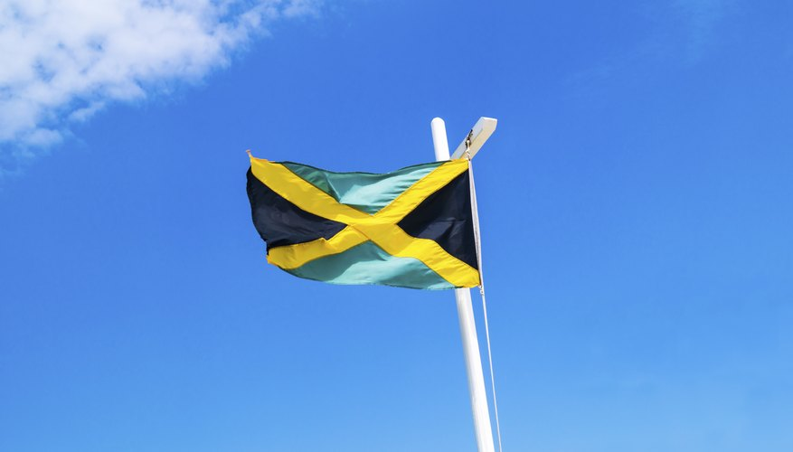 A Jamaican flag flying on the mast of a boat.
