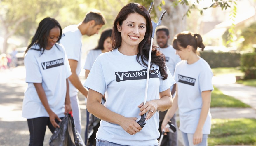 A woman and team volunteering to help clean the community.