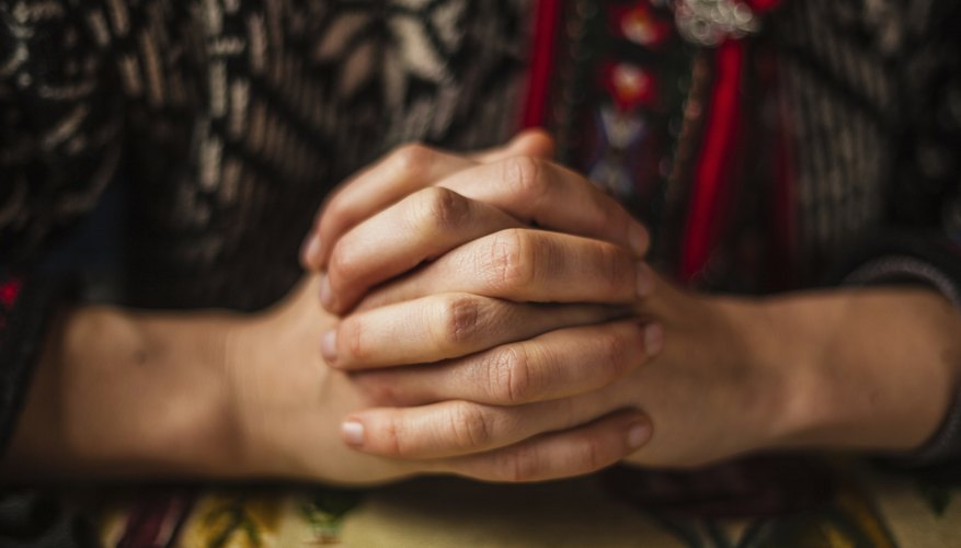 A close-up of a woman clasping her hands in prayer.