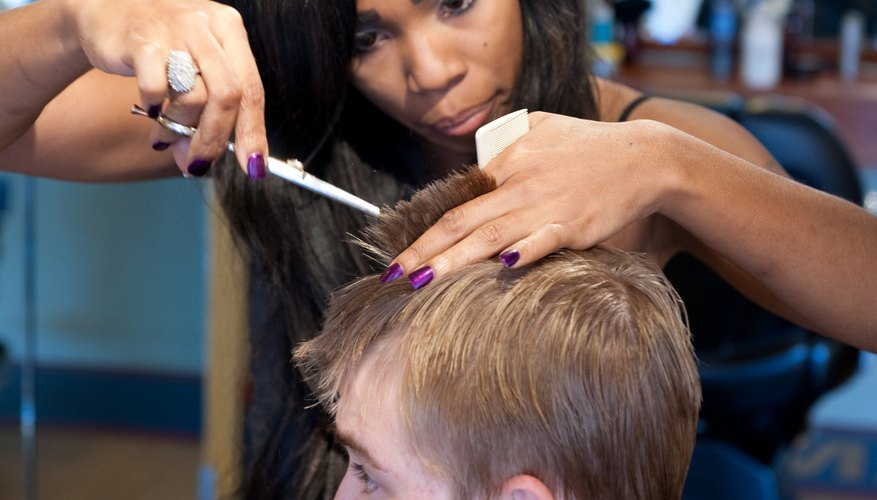 A cosmetologist cuts a young man's hair in a salon.