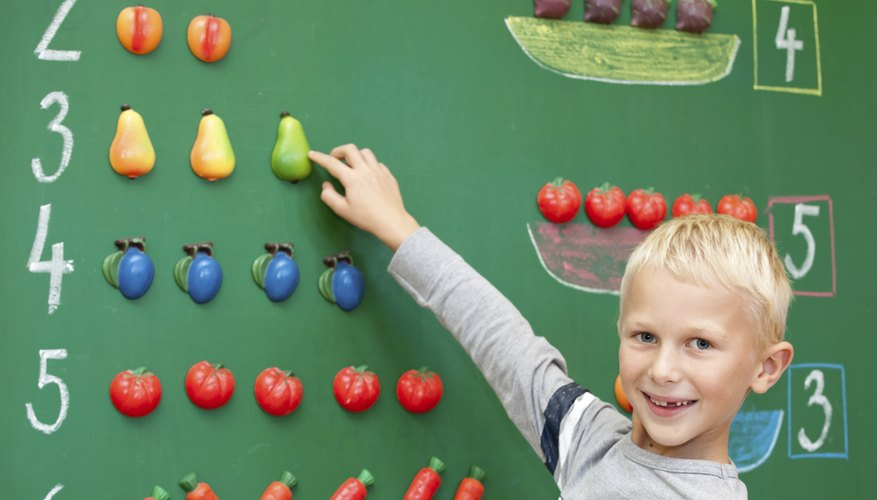 First grader counting numbers on chalkboard