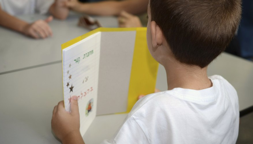 First grader holding up small book.