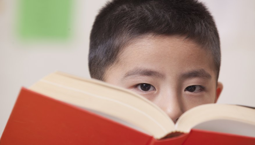 Close-up of student looking over book in classroom.