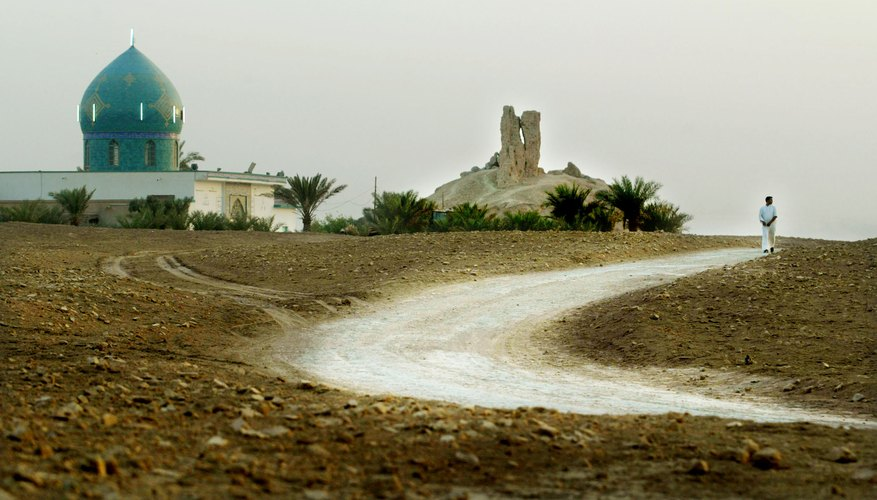 A road winds through a Mesopotamian landscape by an ancient shrine.
