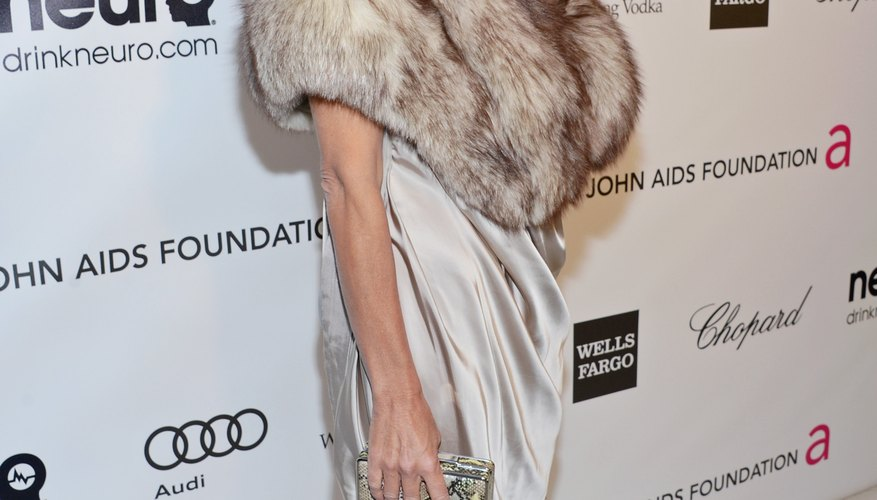 Actress Rachel Griffiths wears a silver dress with a stylish fur wrap in a neutral color.