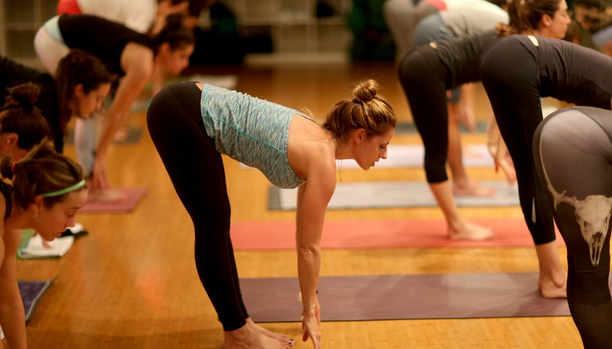 A woman leading a yoga class in a studio.