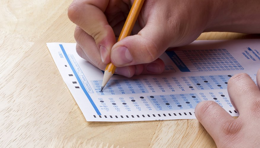 A close-up of a young person filling out a test sheet with a pencil.