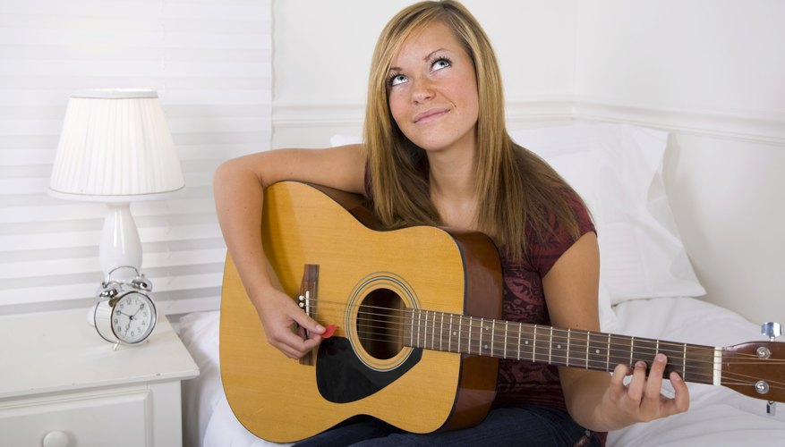 Girl playing guitar in dorm room.
