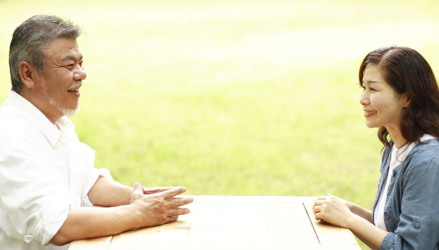 Man and woman having discussion at table.