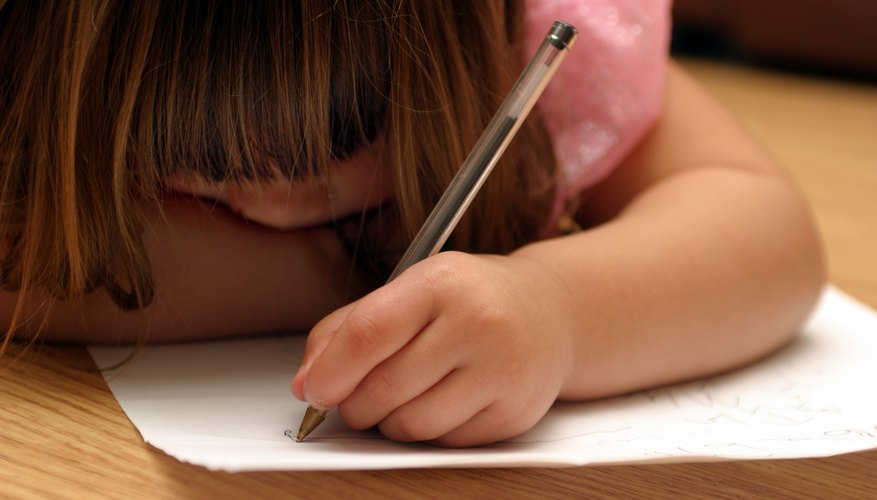 Young child writing with her left hand.