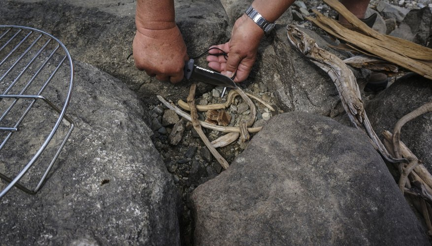 Two hands making fire with flint tool