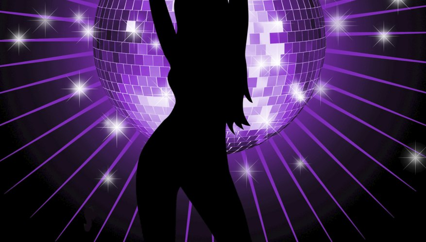 The disco ball sends sparkling light around the room, highlighting the dancers.