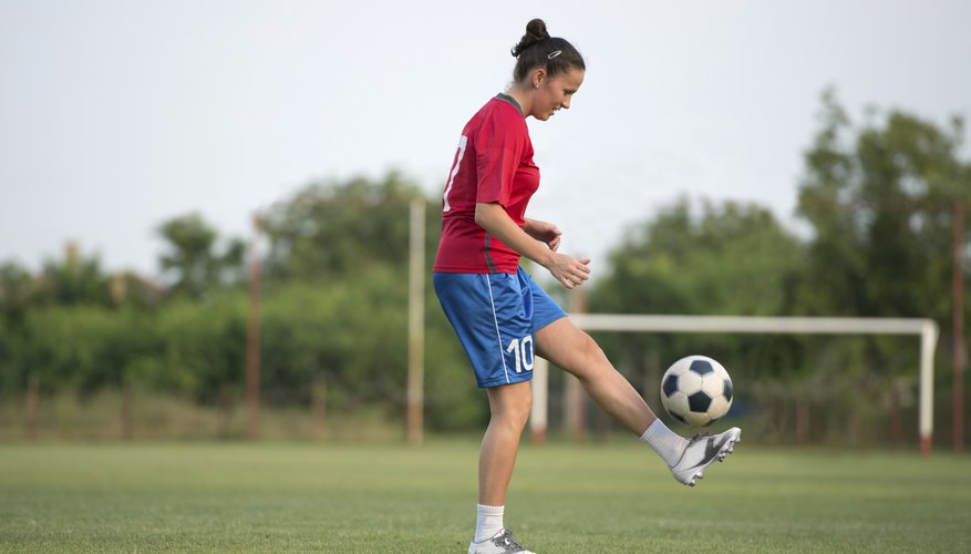 A young woman is kicking the soccer ball.