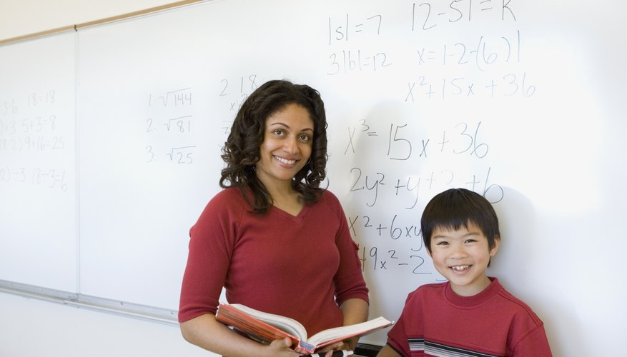 Smiling teacher in classroom with student.