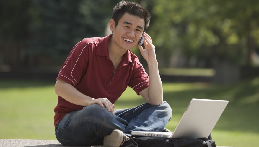 Student working on laptop while talking on cellphone.