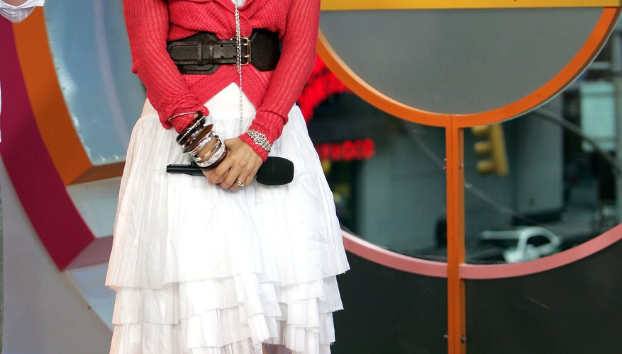 Jennifer Lopez wears a white skirt, red sweater and black pumps for an appearance on MTV's