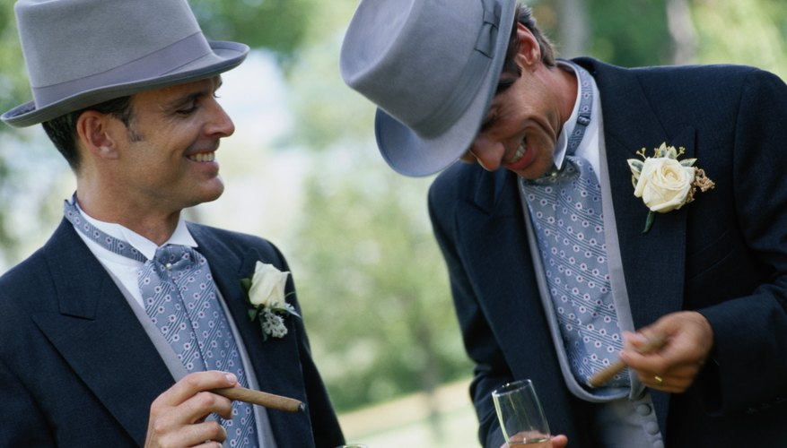 A groom and groomsman laugh and smoke cigars together outside.