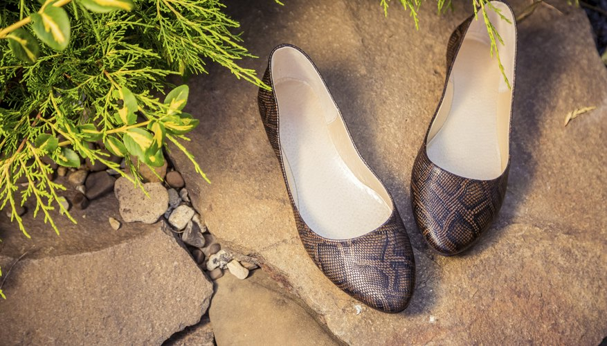 A pair of snakeskin ballet flat shoes on a rock.