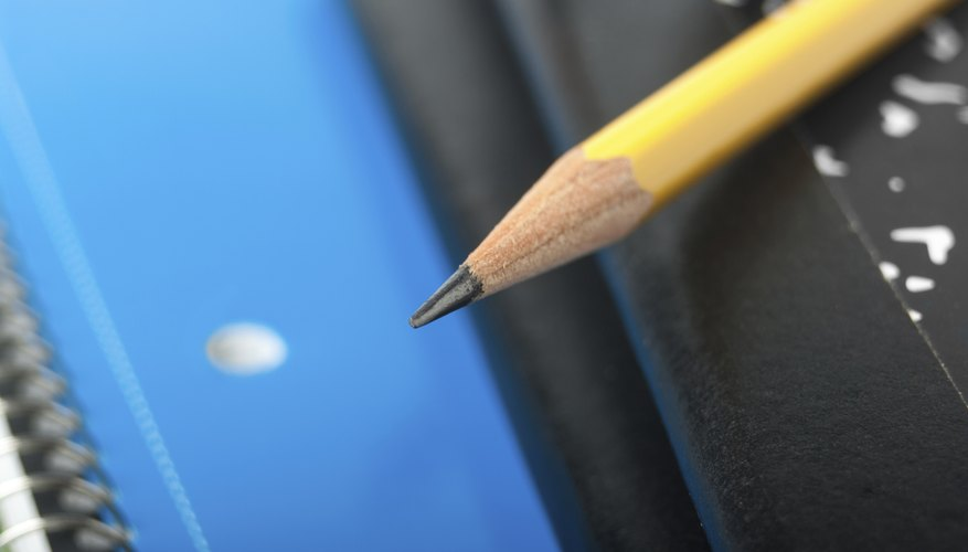 Close-up of pencil sitting on top of notebooks