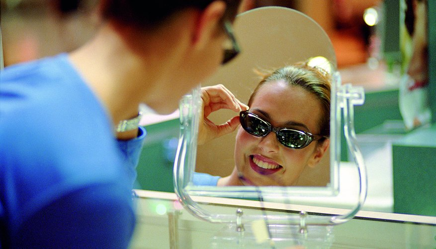 Woman trying on a pair of sunglasses.