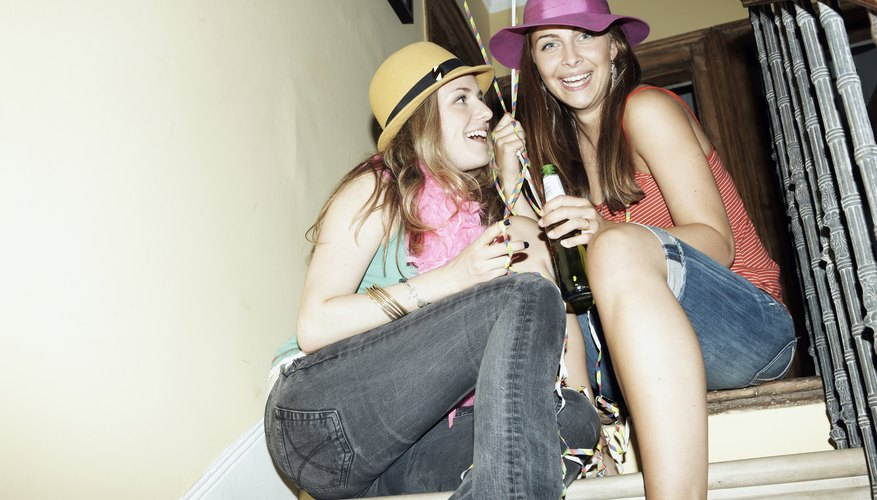 Two sorority girls at a party wearing hats.