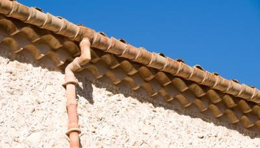 A gutter carries rainwater away from a house and into underground drainage.