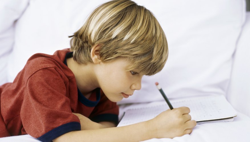 Boy writing on couch
