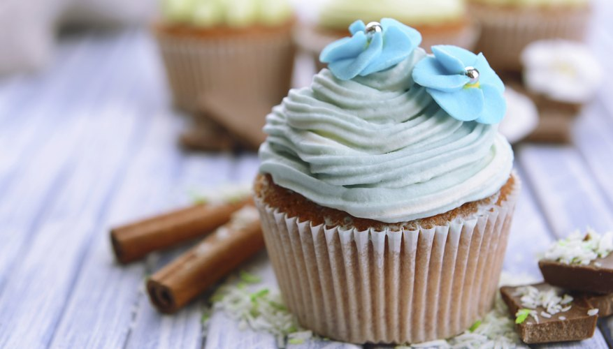 A cupcake with blue icing and garnish.