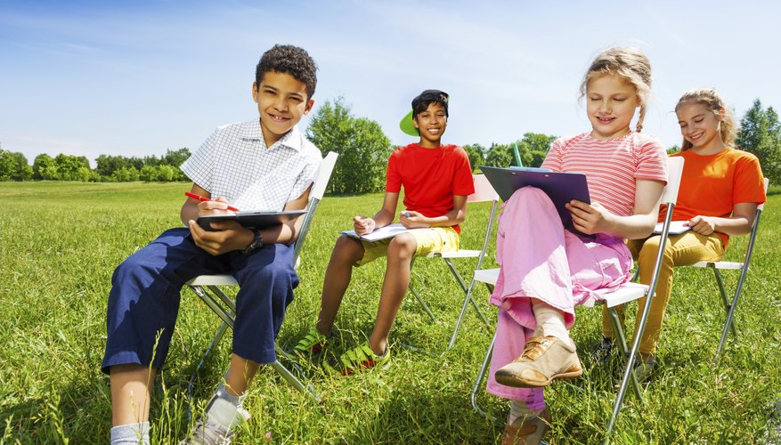 A school nature club sitting outside drawing.