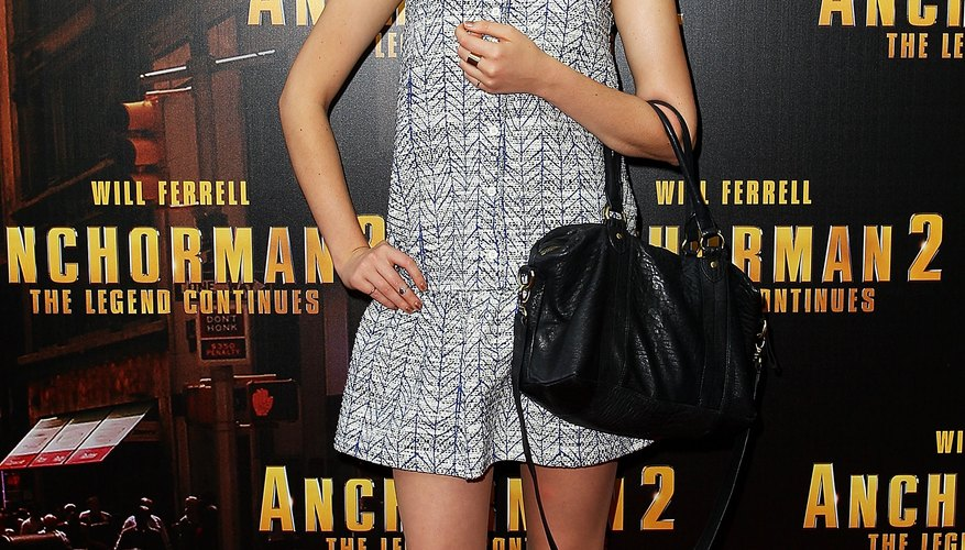 Singer Emma Birdsall wears a gray dress with black ankle boots at the