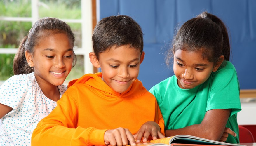 A small group of three children sit and read together