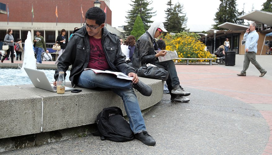 A college student working on a class assignment outside on campus.