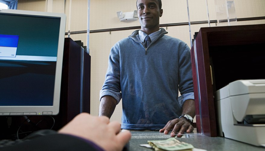 The bank teller requires your signature to cash or deposit a check.