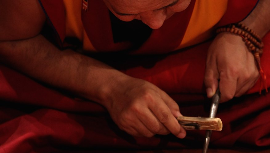 A Buddhist monk creates a sand mandala, symbolizing the impermanent universe.