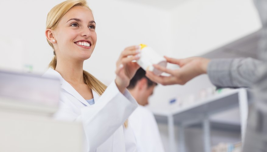 A pharmacist giving drugs to a patient.