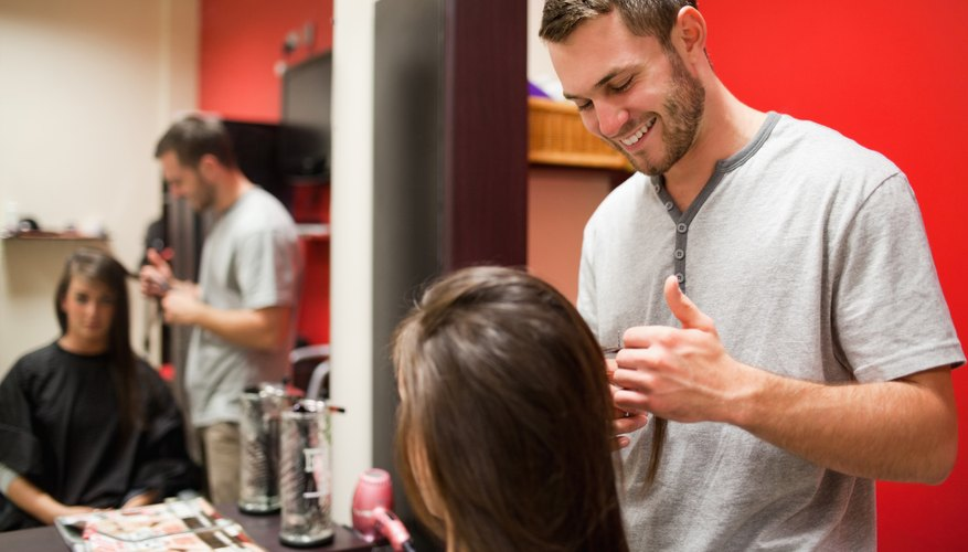 A hair designer talking with his client in a salon.