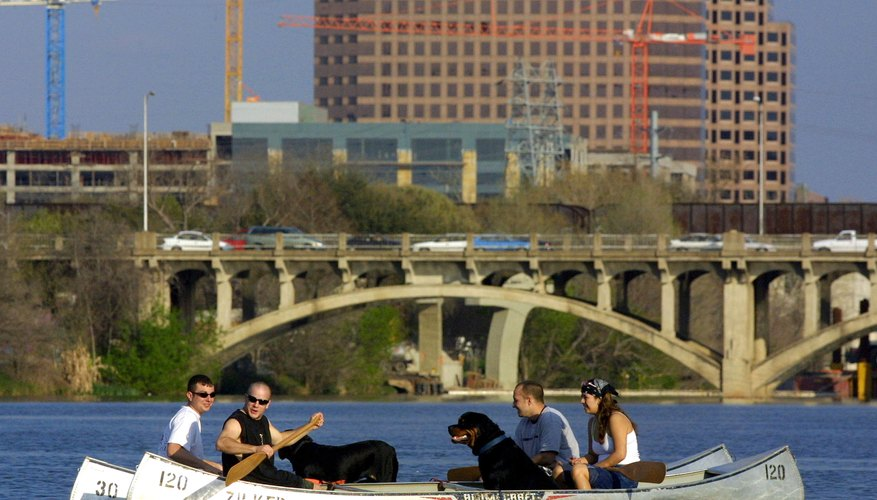 Friends in canoes with dogs paddle on Town Lake (Lady Bird Lake)