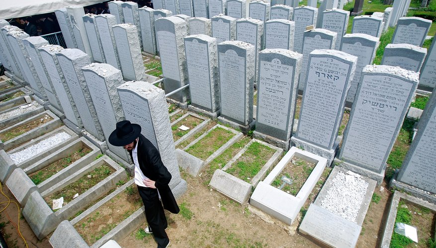 A mourner pays his respects at a Jewish cemetery.