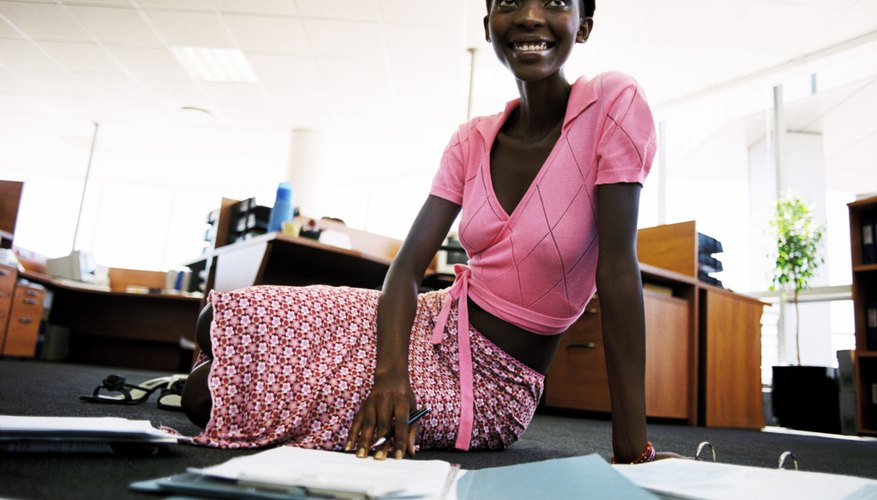 A young woman is doing work in an office.